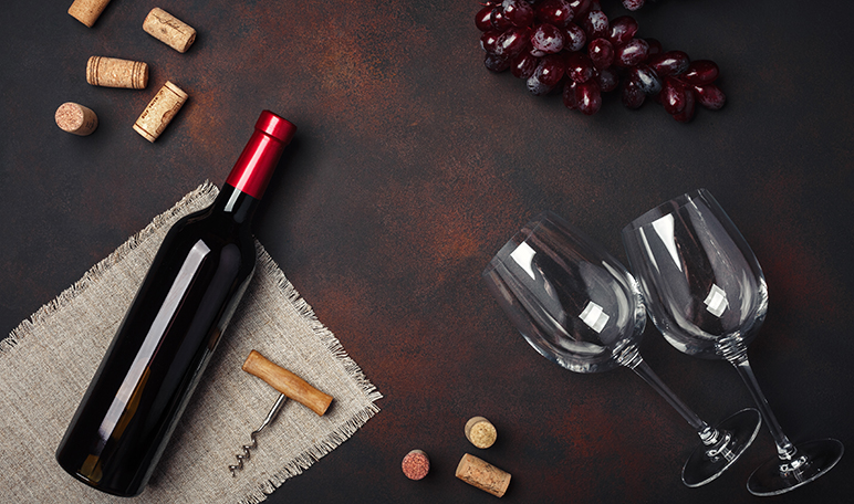 bottle-of-wine-two-glasses-corkscrew-and-corks-on-rusty-background-top-view-copy-space